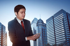 Businessman text messaging. On city background Royalty Free Stock Images