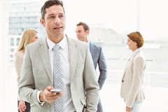 Businessman text messaging with colleagues in meeting behind Stock Photos