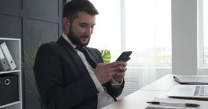 Businessman text messaging on mobile phone stock footage