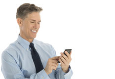 Businessman Text Messaging Through Mobile Phone. Happy mature businessman text messaging through mobile phone against white background Stock Images