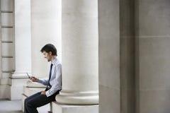 Businessman Text Messaging By Pillar Royalty Free Stock Photos