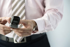 Businessman text messgaging on mobile phone, front view, mid-section, close-up (differential focus) Stock Photography