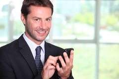 Businessman texting. On a mobile phone Royalty Free Stock Photo