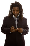 Businessman Texting. African adult male businessman with dreadlocks dressed in business casual texting on his mobile phone Stock Images