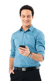 Businessman Texting On Cell Phone. Young Businessman With Hand In Pocket Using Cell Phone Isolated On White Background Royalty Free Stock Photos