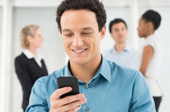 Businessman Texting On Cellphone. Happy Young Businessman Looking At Cellphone In Office Royalty Free Stock Photography