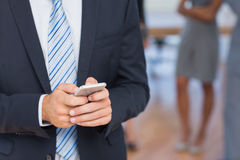 Businessman texting with colleagues behind him Stock Photography