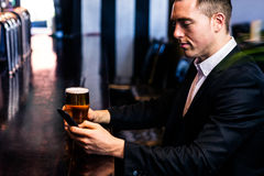 Businessman texting and having a beer Royalty Free Stock Photo