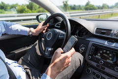 Businessman texting on his mobile phone while driving.