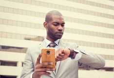 Businessman texting on mobile phone and looking at his watch Stock Photo