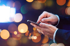 Businessman texting with mobile phone on the street at night Royalty Free Stock Photography
