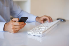 Businessman texting on phone at desk Stock Photo