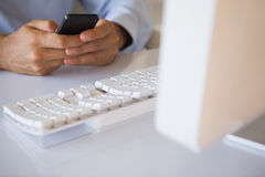 Businessman texting on phone at desk Royalty Free Stock Photography
