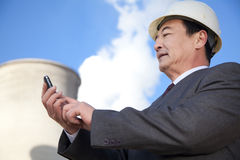 Businessman texting at power plant Stock Images
