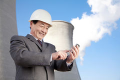 Businessman texting at power plant Stock Image