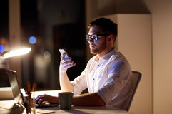 Businessman texting on smartphone at night office. Business, overwork, people, deadline and technology concept - businessman in glasses with laptop computer Stock Image