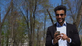 Businessman texting to secretary by phone in slow motion. Arabian man uses phone and smiles in slow motion. Muslim boy has black hair, beard and dimples on face stock video footage
