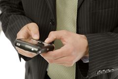 Businessman texts on phone. Businessman uses his thumbs to text on a mobile device Royalty Free Stock Images