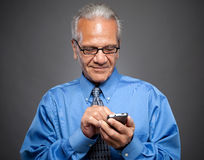 Businessman texts on a smartphone Stock Images