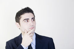 Businessman thinking. Looking to his left with finger on his chest royalty free stock images
