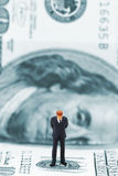 Businessman thinking. Miniature businessman thinking on dollar banknote stock photography