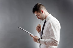 Businessman thinking. A businessman with notepad thinking Stock Photo