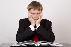 Businessman thinking. Businessman sitting and thinking about books royalty free stock images