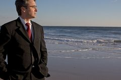 Businessman thinking on the beach royalty free stock photography