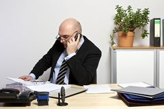 Businessman is thinking, while he bends over a folder Royalty Free Stock Photo