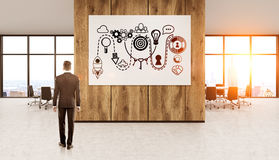 Businessman thinking about business development. Businessman in dark suit standing in sunlit office in front of poster with abstract sketches thinking about Stock Images