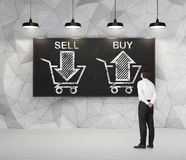 Businessman is thinking about the choice 'sell or buy', arrows on the blackboard. Stock Image