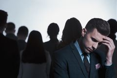 Businessman thinking in a crowd Royalty Free Stock Photos