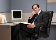 Businessman thinking at desk in cubicle. Serious businessman thinking at desk in cubicle Royalty Free Stock Images