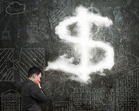 Businessman thinking about dollar sign shape cloud with doodles Royalty Free Stock Photos