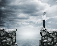 Businessman thinking at the edge of a cliff Stock Photo