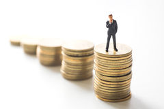 Businessman thinking in front of coins Stock Images