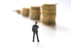 Businessman thinking in front of coins. Stacks. Investment concept royalty free stock photo