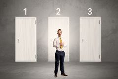 Businessman thinking in front of three doors Stock Photo