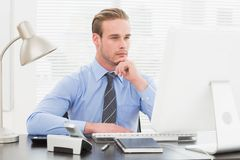 Businessman thinking with hand on chin Stock Image