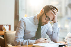 Businessman thinking hard. Bearded pensive businessman in shirt and tie sitting in cafe bent over notepad, holding head with his hand and thinking hard over Stock Images