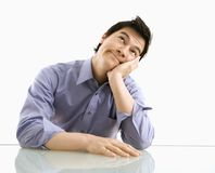 Businessman thinking and hoping. Young Asian business man sitting daydreaming Stock Photography