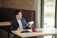 Businessman Thinking Ideas Strategy Working Concept In a cafe. Handsome businessman is looking out the window and smiling Royalty Free Stock Images