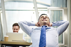 Businessman thinking in office. Caucasian business person sitting in office thinking daydreaming hands behind head Stock Photography