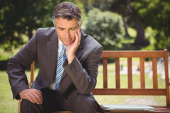 Businessman thinking in the park Royalty Free Stock Image