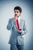 Businessman thinking. Businessman portrait grey background with his hand on chin thinking Royalty Free Stock Images
