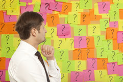 Businessman thinking with question marks written Stock Photos