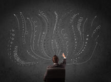 Businessman thinking with sketched arrows in front of a chalkboa Stock Photos