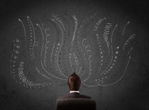 Businessman thinking with sketched arrows in front of a chalkboa Royalty Free Stock Image