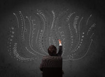 Businessman thinking with sketched arrows in front of a chalkboa Royalty Free Stock Photo