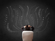Businessman thinking with sketched arrows in front of a chalkboa Stock Image